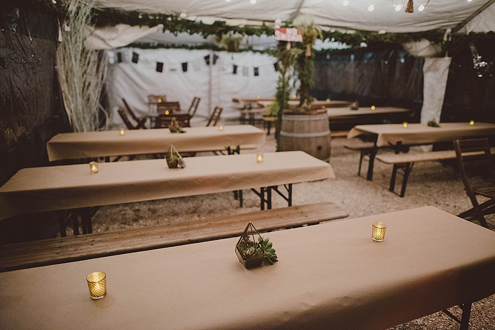 The wedding reception was done with much greenery, succulent terrarium centerpieces, candles and kraft paper