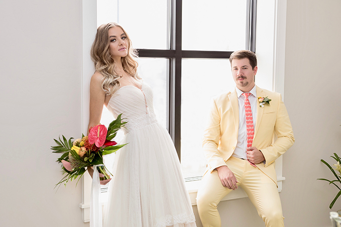 The groom was wearing a bright yellow suit and a bright coral printed tie to match the wedding theme