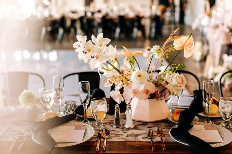 The tablescape was done in blush and black, too, with lush floral centerpieces, elegant cutlery and a printed runner