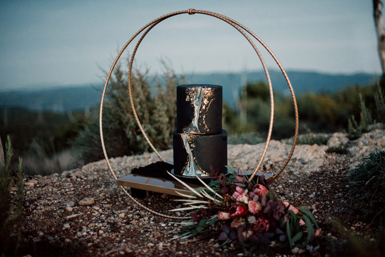 The wedding cake was black, with metallic touches and a marble effect and it was served on a moon-lliek stand