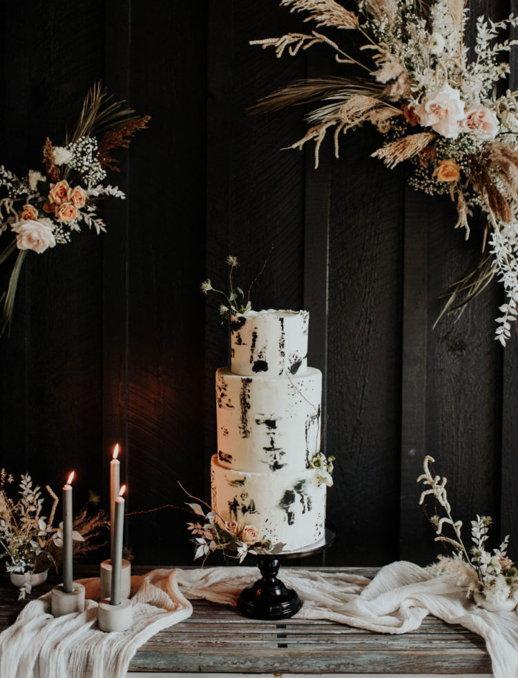 The wedding cake was white, with black brushstrokes and some dried blooms on top