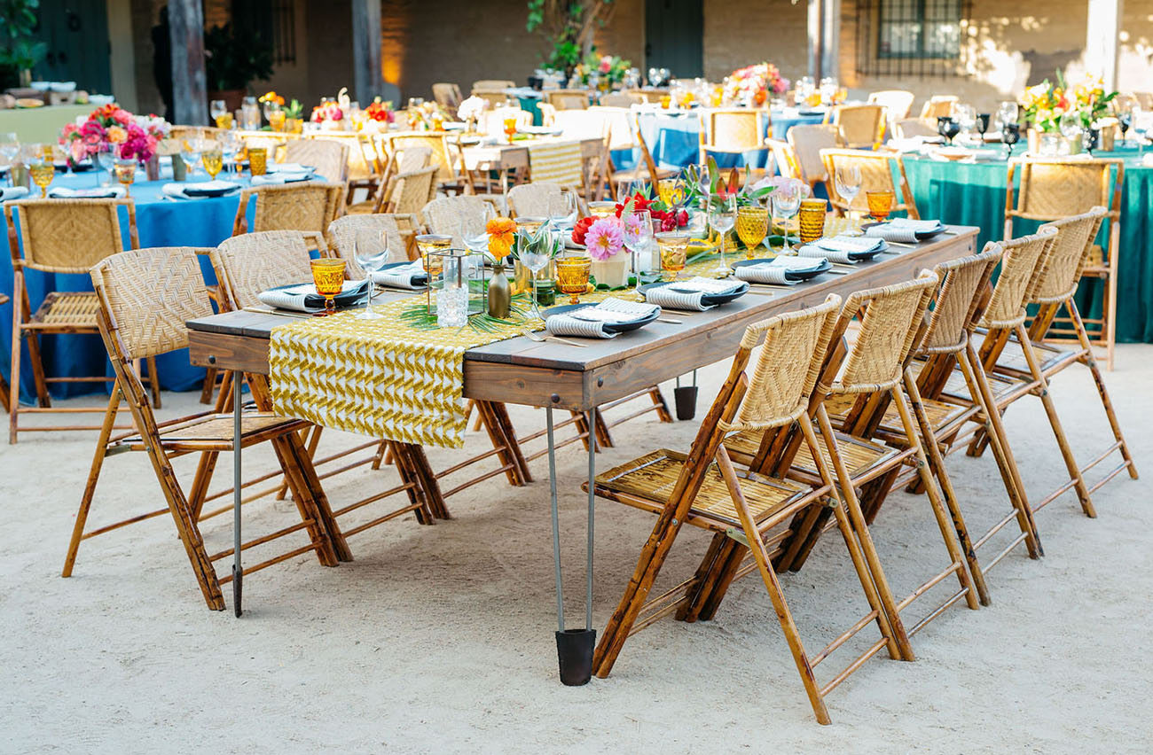 The wedding table settings were done with printed table runners, bright blooms and glasses