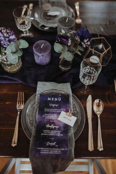 a decadent grey and purple wedding table setting with greenery, purple candles and menus and geometric touches