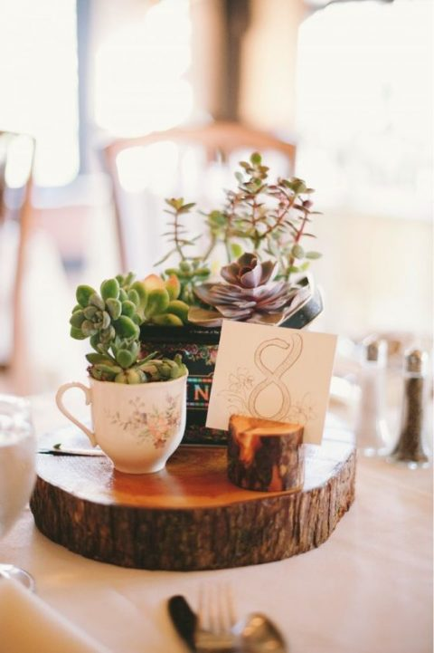 a simple and cute rustic wedding centerpiece with wood slices, a tin can and a cup with succulents and a table number