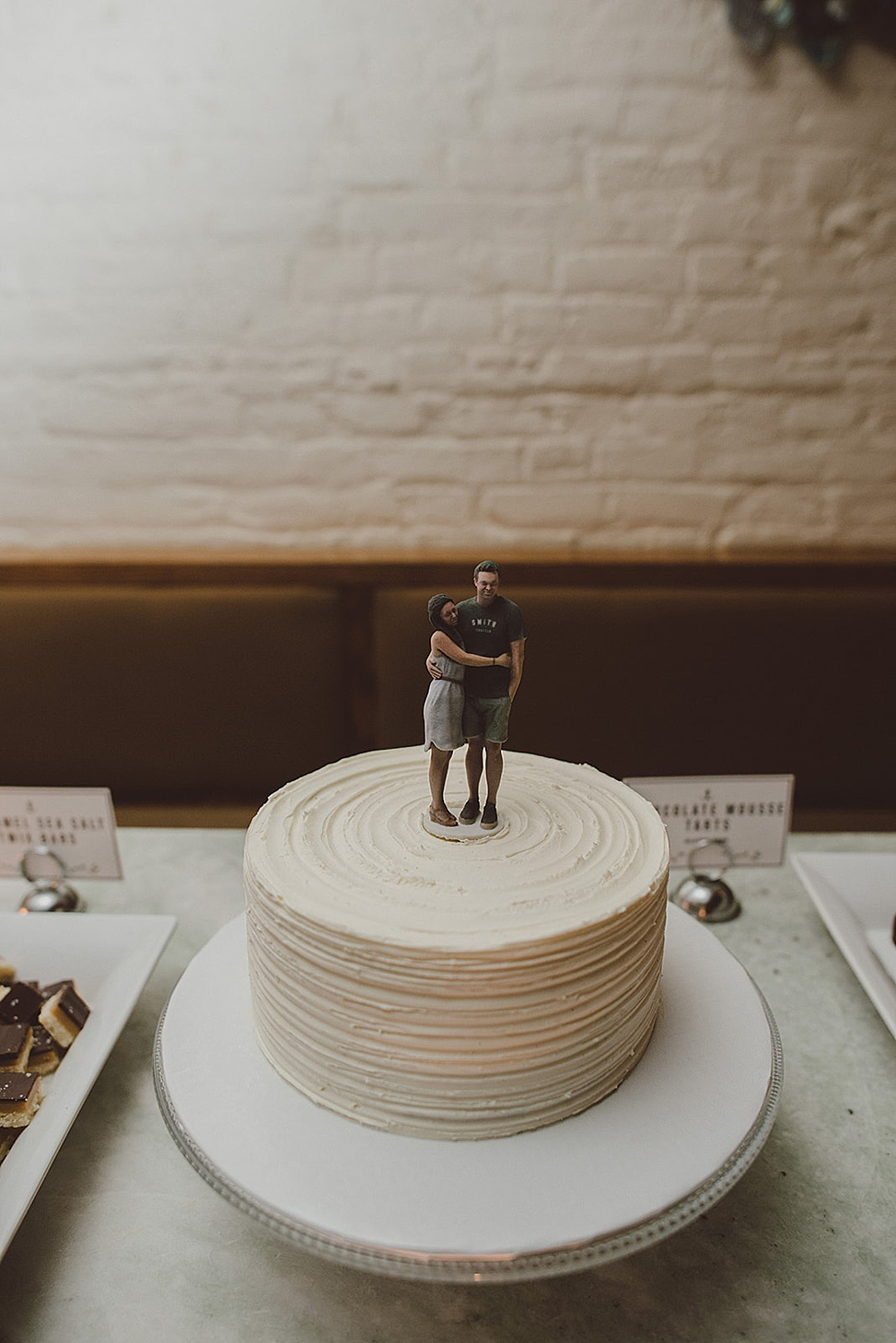 The wedding cake was casual and white, with the couple's figurines on top   so cute