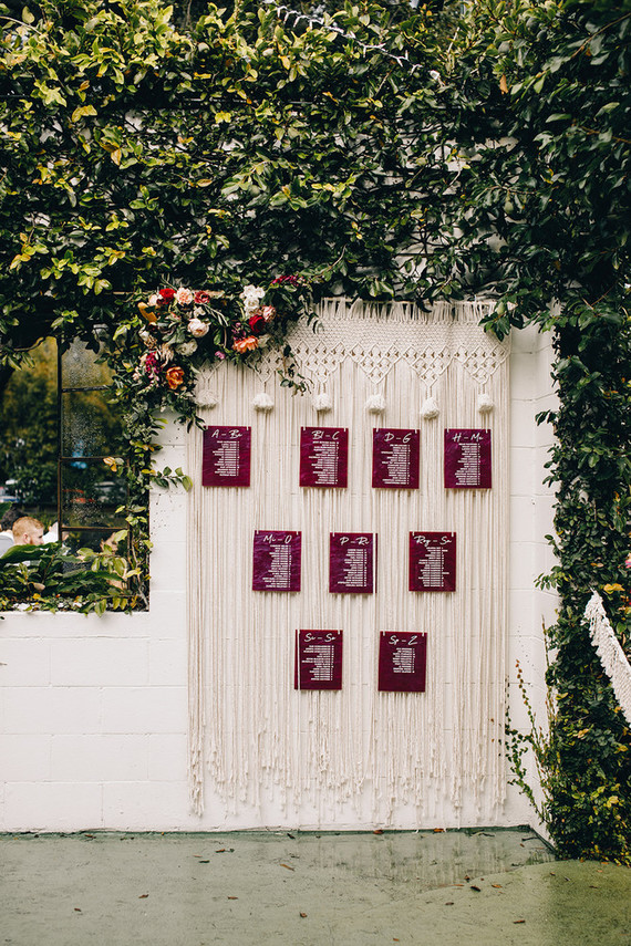 The wedding seating chart was done with macrame and burgundy seating cards plus blooms