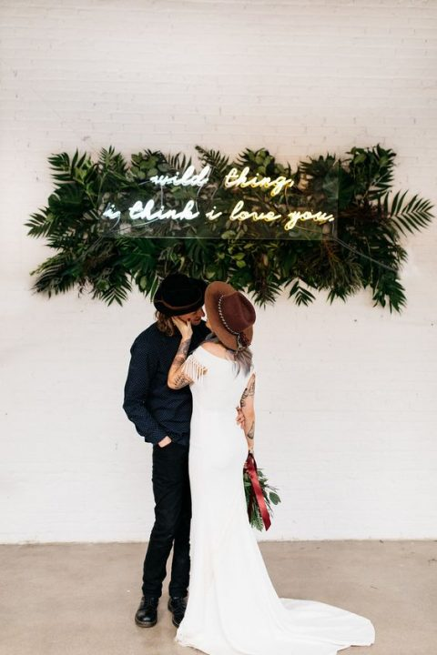 a modern boho wedding backdrop with tropical leaves and a neon sign is a fun idea