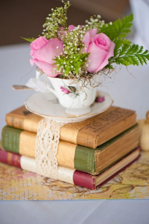 a stack of vintage books with a lace tie, a teacup with pink roses and greenery for a wedding centerpiece
