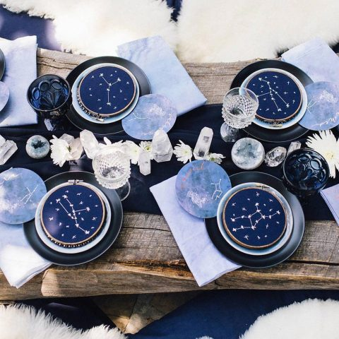 a modern celestial wedding tablescape done with an uncovered wooden table in purple, navy and black, with costellation detailing and crystals