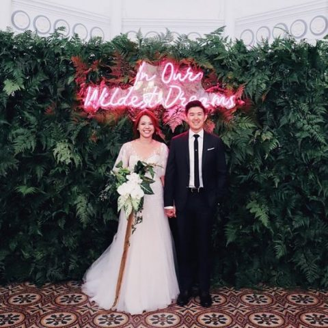 a modern wedding backdrop of lush greenery and a red neon sign is a statement idea