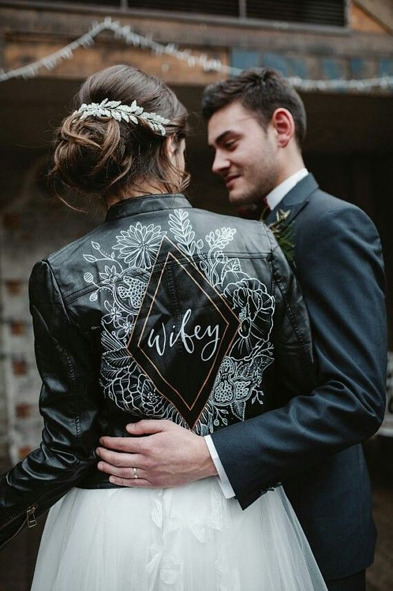 a beautiful black leather jacket with handpainting is a bold and edgy idea for a modern bride