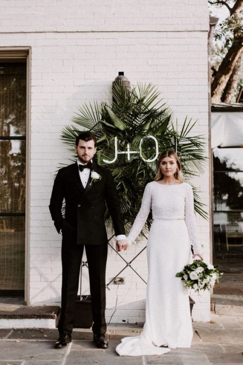 a modern wedding backdrop with a white brick wall, a tropical leaf arrangement and neon monograms