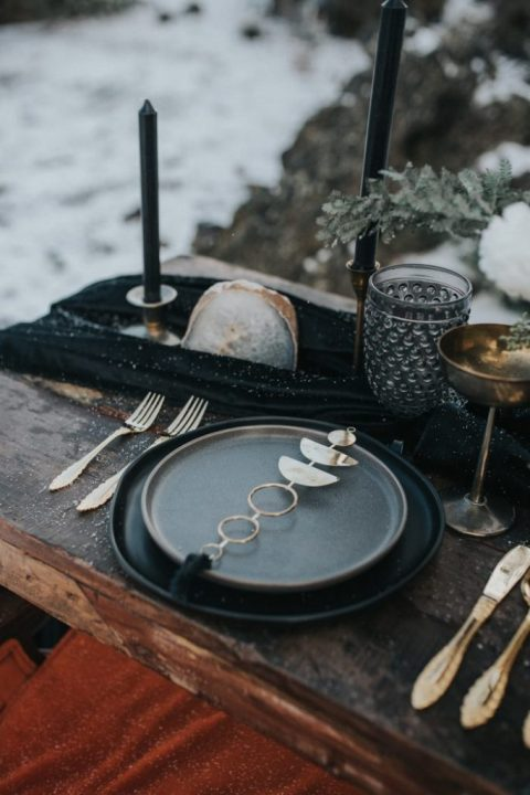 a moody celestial wedding place setting done in black and grey, with a half moon napkin holder, candles, geodes and metallics