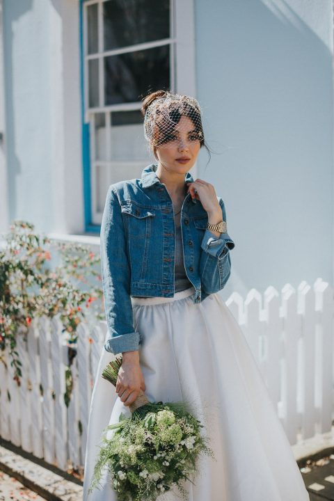 a casual yet edgy bridal look with a plain maxi skirt, a grey top, a denim jacket and a cage veil
