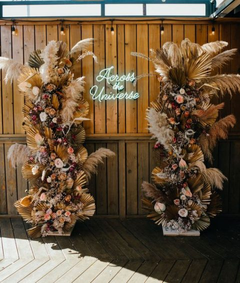 a stunning boho wedding altar with lush blooms, dried fronds and pampas grass and a neon sign