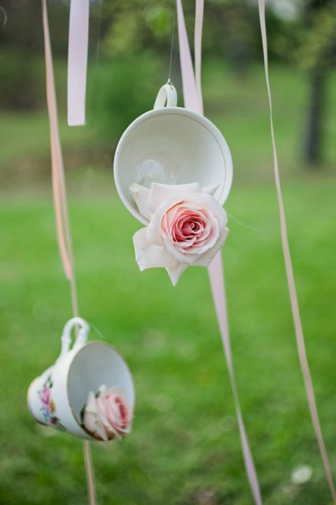 suspended vintage teacups with pink roses on ribbons is a beautiful decor idea for a dessert wedding