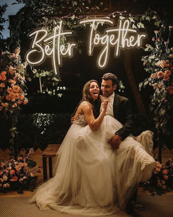a bold neon sign in the photo zone or reception is a cool idea, add lush florals for more romance