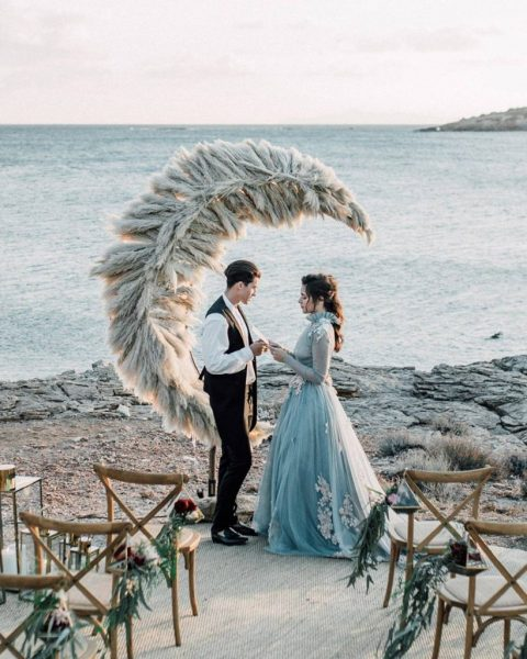 a unique half moon wedding altar made of pampas grass and placed right on the seashore is a gorgeous idea to try