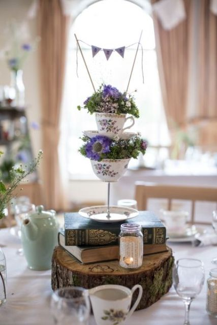 a vintage meets rustic wedding centerpiece with a wood slice, books, teacups on a stand, bright blooms and a banner