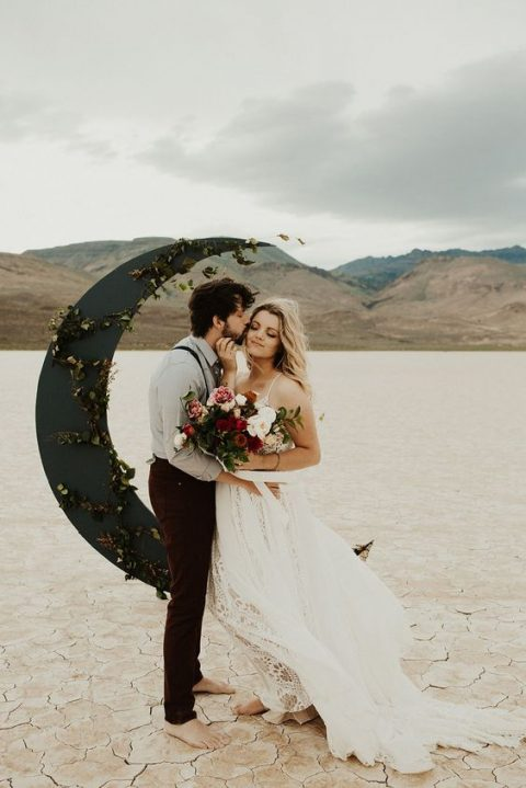 an unusual black half moon wedding altar decorated with foliage and placed in the desert