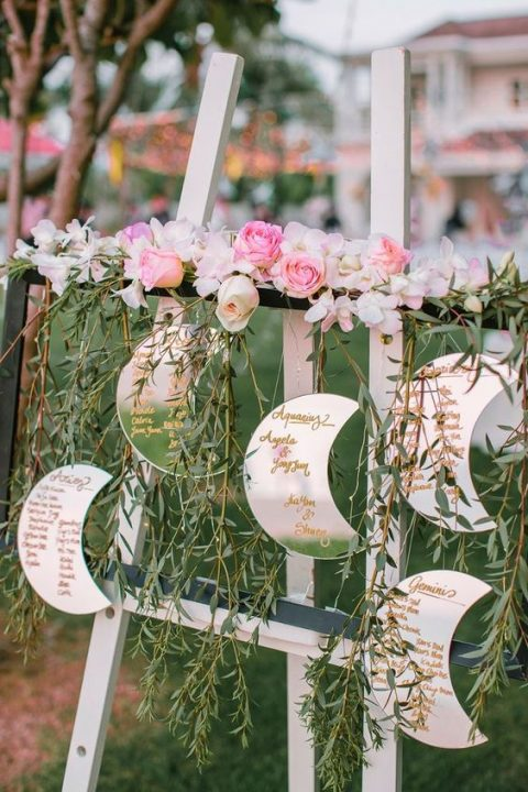 a half moon wedding seating chart done with lush blooms and greenery is a perfect idea for a celetial wedding