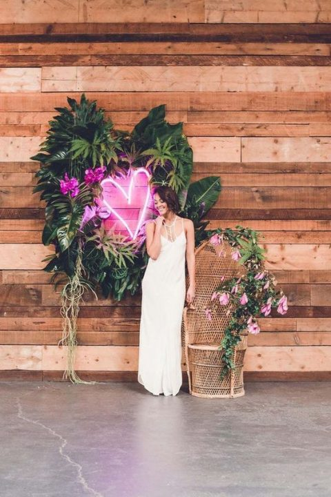 a lovely wedding decoration with a round tropical greenery wreath and a pink neon heart in the center