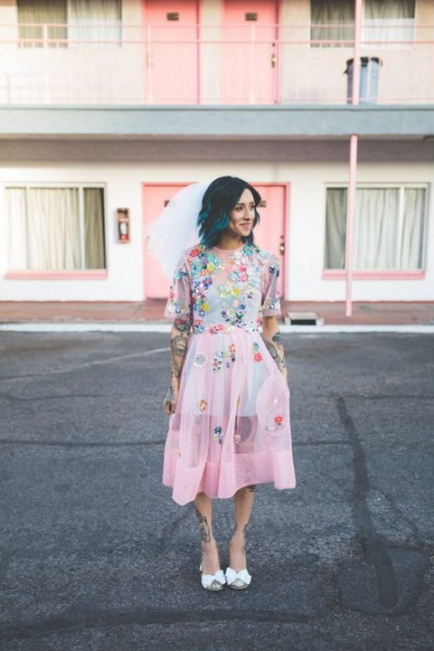 a badass bride wearing a pink wedding dress with colorful floral appliques, bow shoes and teal hair