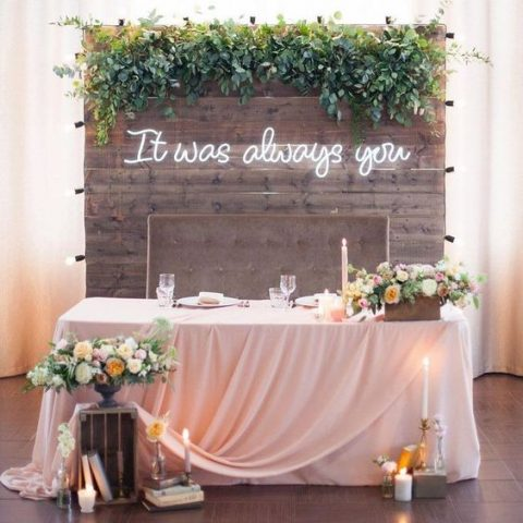a rustic wooden wall with greenery decor and a neon sign for the reception or sweetheart table backdrop