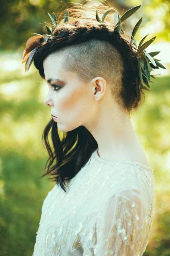 a braided and messy hairstyle with a half shaved head and some greenery integrated into the hairstyle