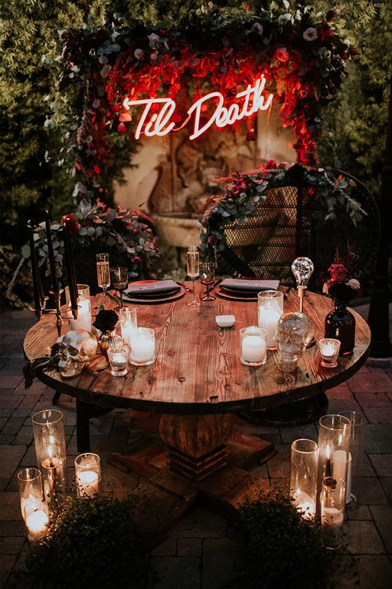 a stylish idea for a Halloween wedding - a neon sign spruced up with lush red blooms and greenery