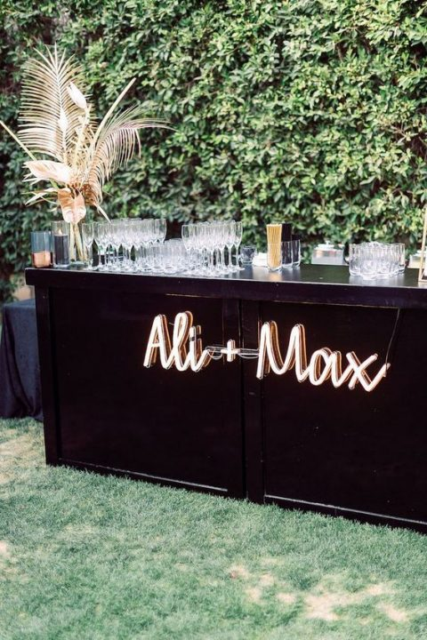 a wedding drink bar decorated with dried fronds and leaves and a neon sign on it