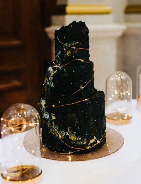 a black textural wedding cake showing off space and decorated with LEDs to mark stars