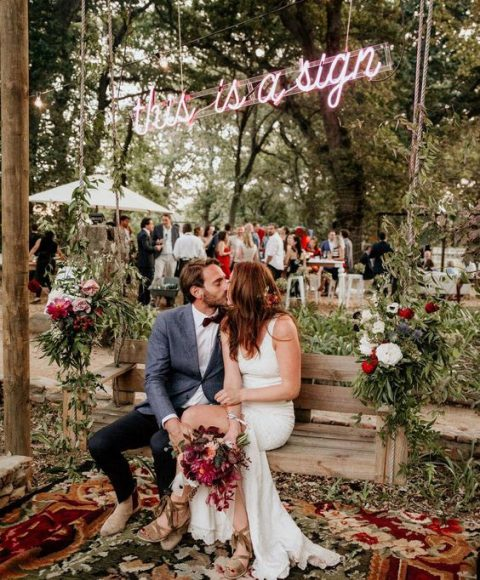 a wedding lounge with a hanging bench, rugs and a neon sign over the bench
