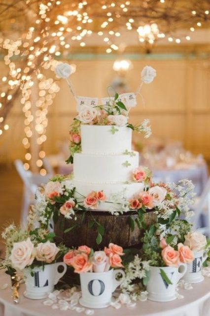 a beautiful wedding cake surrounded with LOVE cups with blooms is a very cute idea of displaying your cake