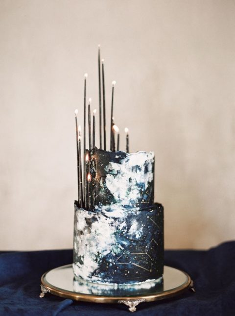 a dark navy and black watercolor wedding cake with constellations and thin black candles brings that wow factor