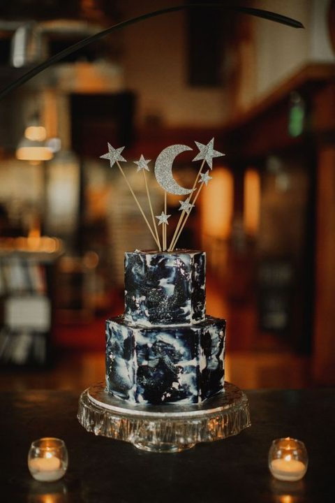a dark watercolor wedding cake topped with silver glitter stars and moon on a shiny silver stand