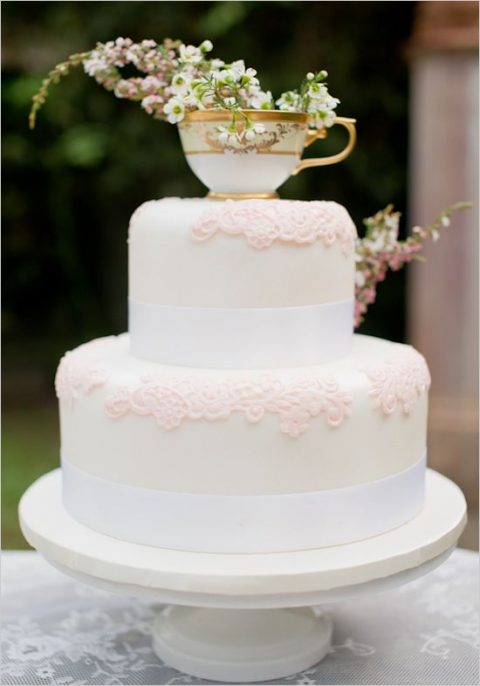a vintage-inspired wedding cake with pink sugar lace, ribbons and a teacup with blooms on top