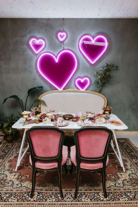 a wedding reception table with a pretty neon pink heart backdrop is a modenr take on classics
