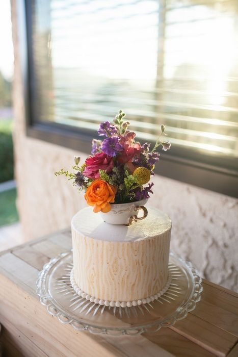 a wedding cake topped with a vintage teacup and lots of colorful blooms to make it bolder