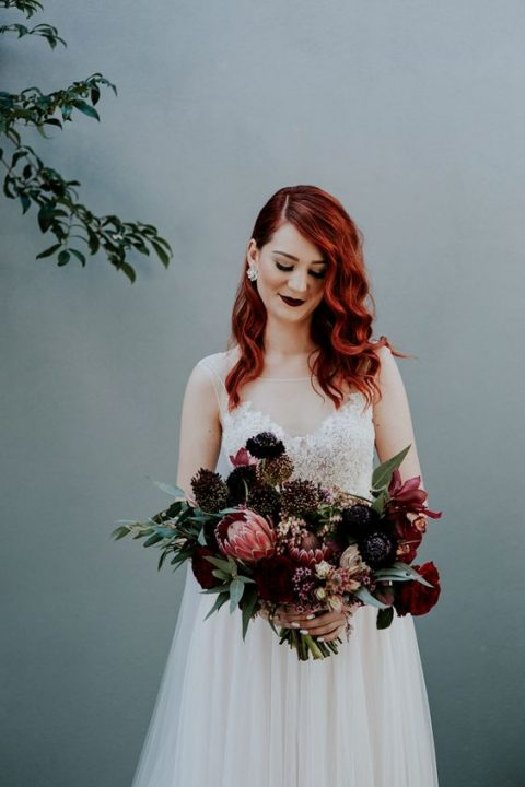 red hair and a very dark burgundy lip make a bold statement, while a romantic wedding dress softens the look