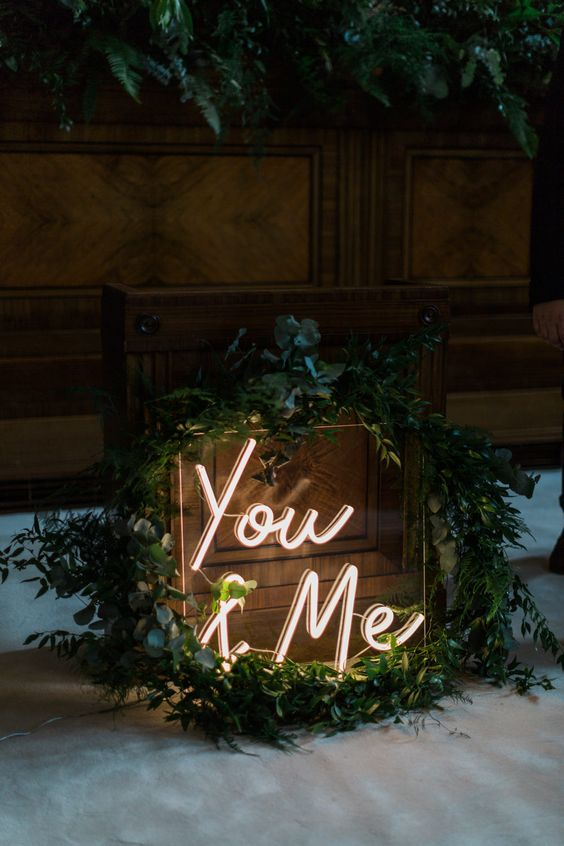 such a small wedding neon sign spruced up with greenery is a cool and modern idea for the wedding reception
