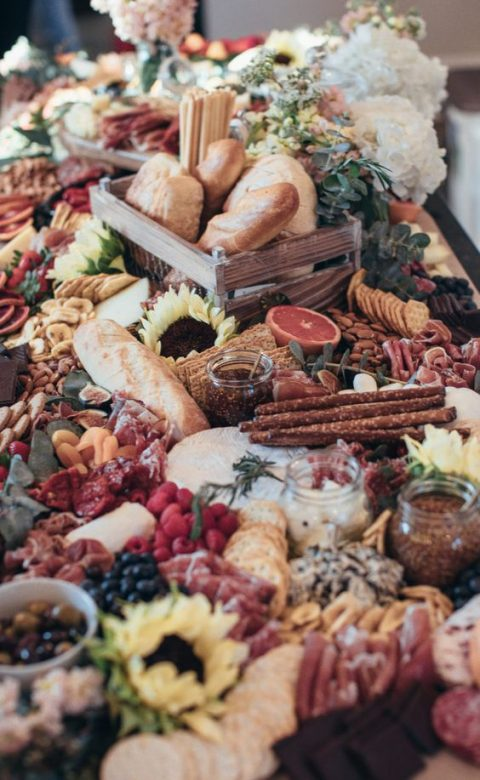 a beautiful grazing table with various kinds of bread, charcuterie, berries and fruit, crackers and dips in jars