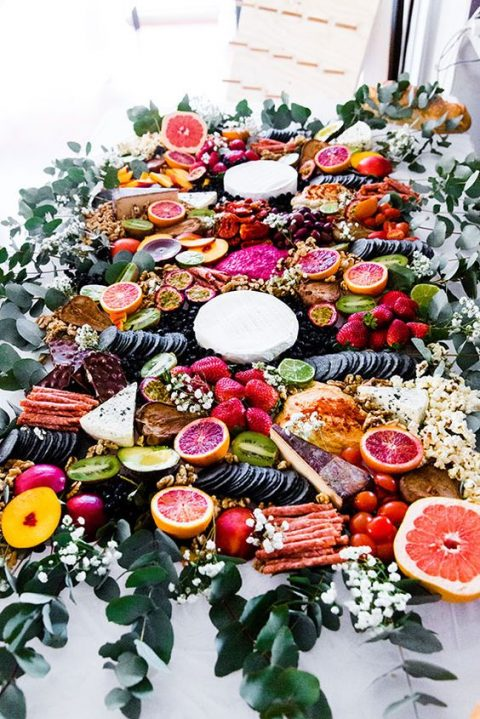 a bright grazing table with cheese, fruits and berries and crackers pls baby's breath and greenery for decor