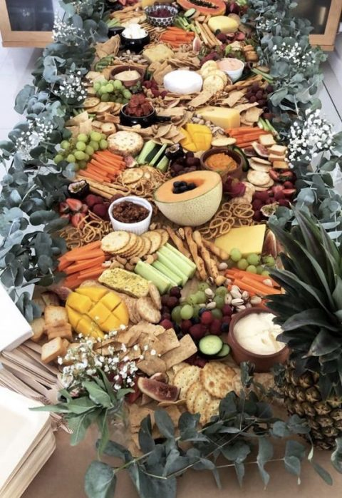 a chic grazing table with crackers, fruits and berries, veggies and nuts plus greenery for decor