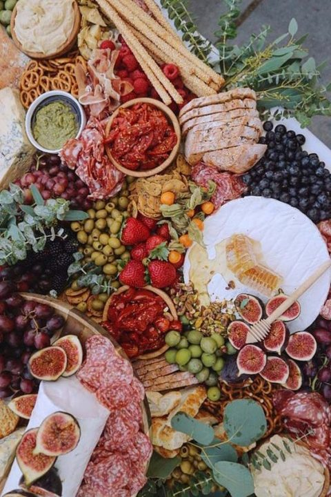 a delicious grazing table with charcuterie, olives, honey, bread and dips of various kinds