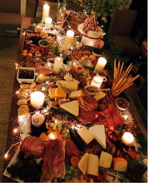 a delicious grazing table with various types of cheese, charcuterie, bread and crackers, some fruit and olives and candles and lights