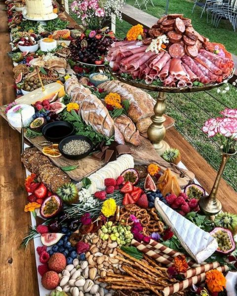 a grazing table done with different layers to incorporate everything from bread sticks and fruits to proschiutto and various sauces