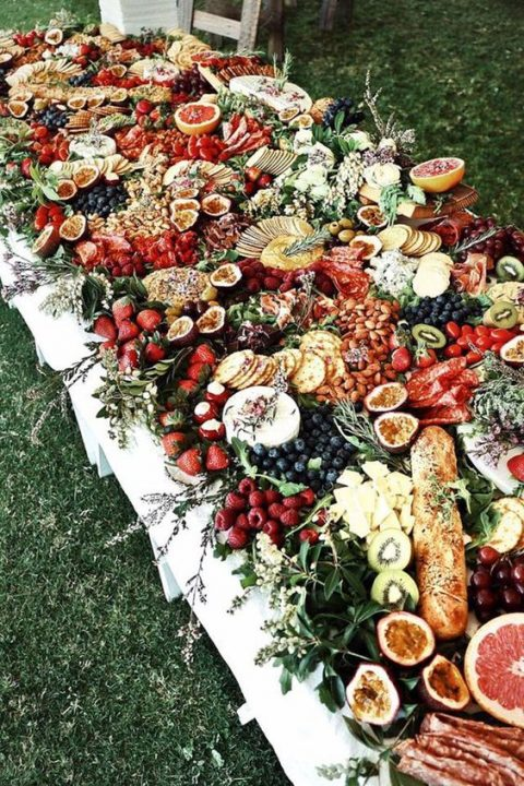 a grazing table with lots of berries and fruit, bread and cheese, herbs and even wildflowers for decor