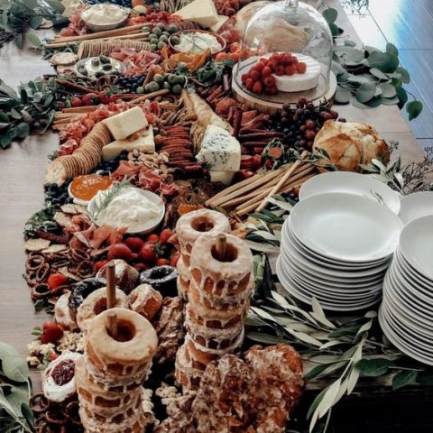a cool grazing table decor with donut stands