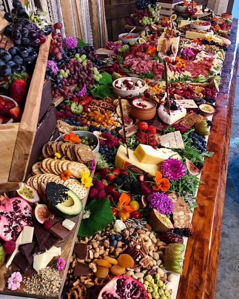 a lush and colorful grazing table with crackers, fruits and berries, nuts and dried fruit, dips and bright blooms
